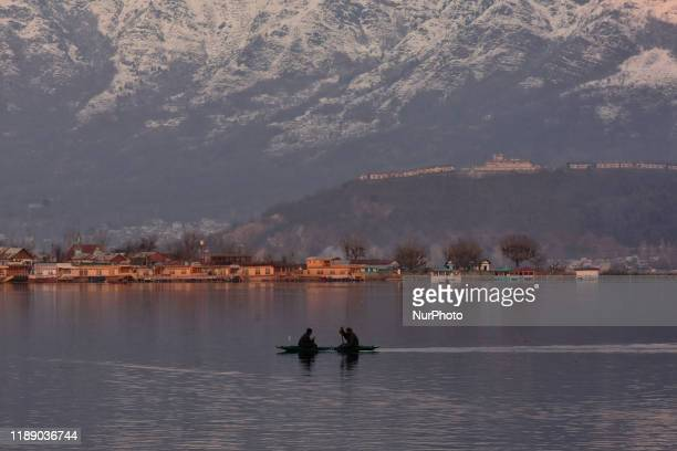 Kashmiri boatman rides his boat in Dal Lake Srinagar on a sunny day in Indian Administered Kashmir on 16 December 2019.