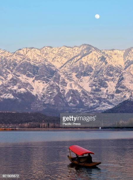 Kashmiri boatman rows a Shikara on the waters of world famous Dal Lake with a snowclad mountain at it's backdrop in Srinagar the summer capital of...