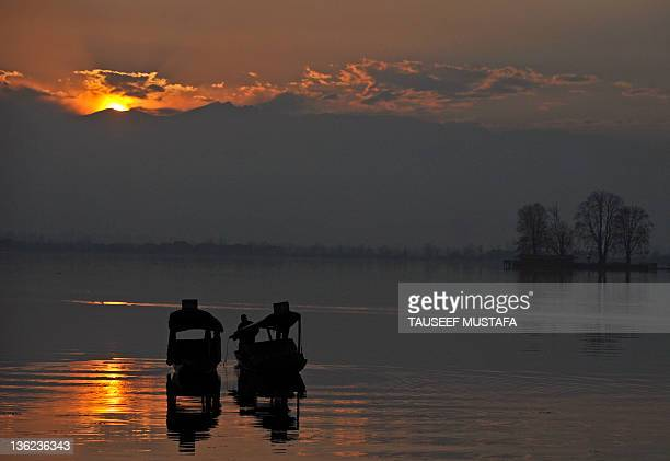 Kashmiri boatman rows his boat during sunset on Srinagar's dal lake on December 29,2011. A cold wave further tightened its grip in Jammu and Kashmir...