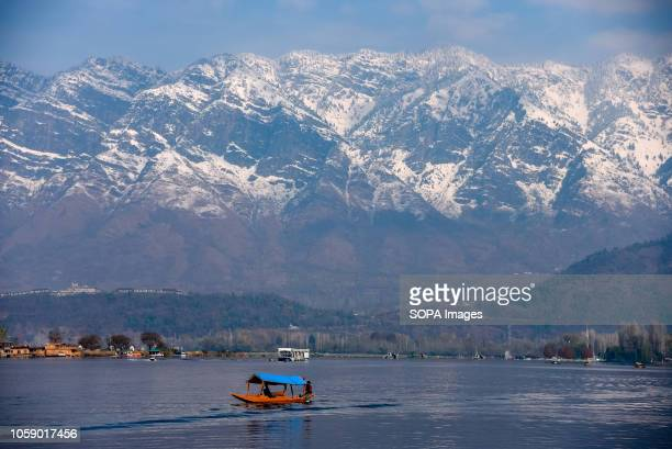 Kashmiri boatman seen rowing his boat on Dal Lake on an evening in srinagar Kashmir has been divided between India and Pakistan since their partition...