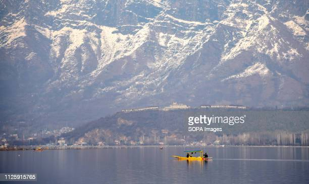 Kashmiri boatman seen rowing his boat on Dal Lake with a backdrop of Snow covered zabarwan mountain during a sunny day in Srinagar Kashmir has been...