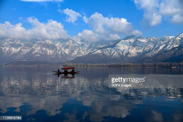 Kashmiri boatman seen rowing his boat on Dal Lake with a backdrop of Snow covered zabarwan mountain during a sunny day in Srinagar. Kashmir has been...