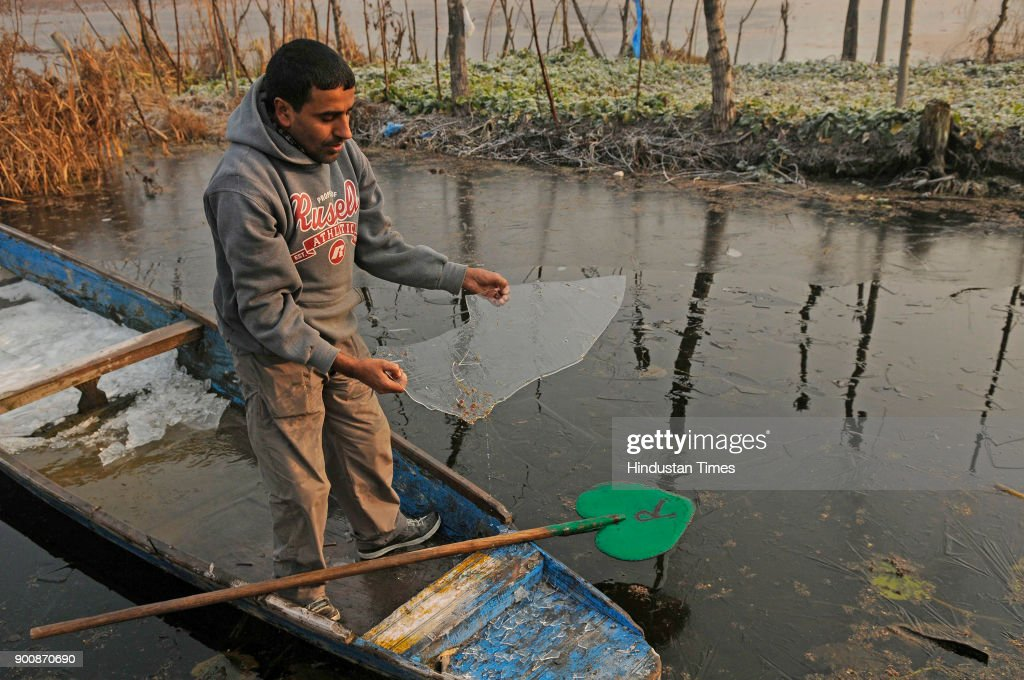 A Kashmiri boatman shows a piece of frozen ice in the interiors of Nigeen Lake on January 3, 2018 in Srinagar, India. The weather in the region continued to remain dry even as the valley remains in a grip of cold wave with temperature in the night dropping to below freezing point.