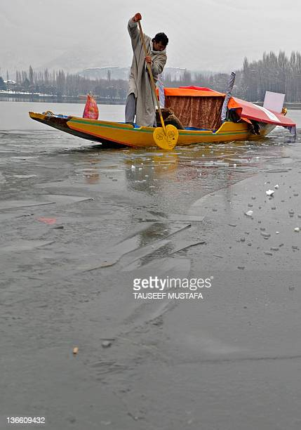 A Kashmiri boatman uses his oar to break through ice on Dal Lake in Srinagar on January 9 2012 A cold wave further tightened its grip in Jammu and...