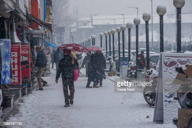 A Kashmiri boy clears the snow covered footpath near his shop amid fresh snow fall on January 16 2019 in Srinagar the summer capital of Indian...