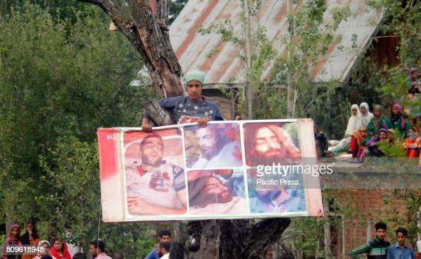 Kashmiri boy displays picture of commander Burhan Wani during the funeral prayers of Jehangir Ahmad Khanday of Keller area of Shopian district Six...