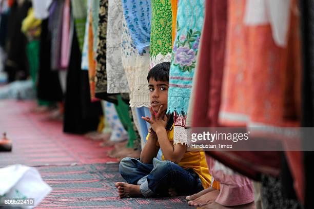 Kashmiri boy looks up as Kashmiri women offer prayers at the Hazratbal Shrine on September 21 2016 in Srinagar India People are holding special...