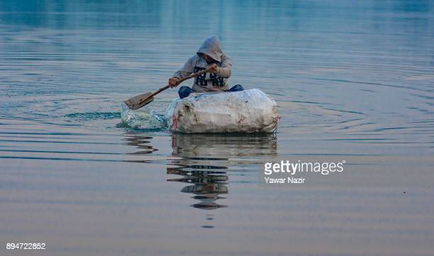 Kashmiri boy paddles his raft in a lagoon which he made from rubbish on a cold day on December 18 2017 in Srinagar the summer capitol of Indian...