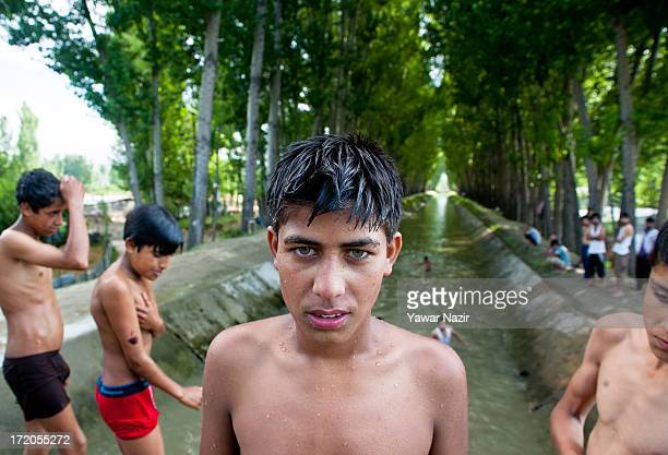 Kashmiri boys jump and swim in a canal on July 01 2013 on the outskirts of Srinagar the summer capital of Indian administered Kashmir India With a...