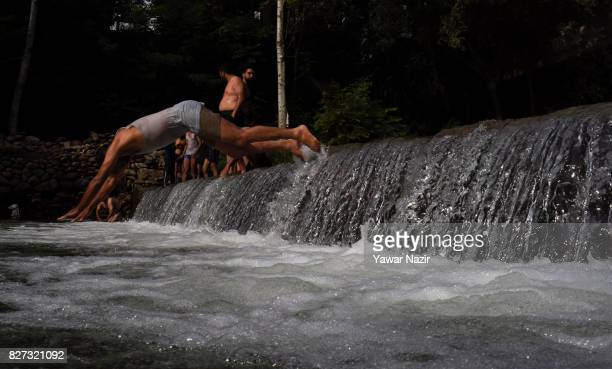 Kashmiri boys jump and swim in a stream on August 07 2017 on the outskirts of Srinagar the summer capital of Indian administered Kashmir India With a...