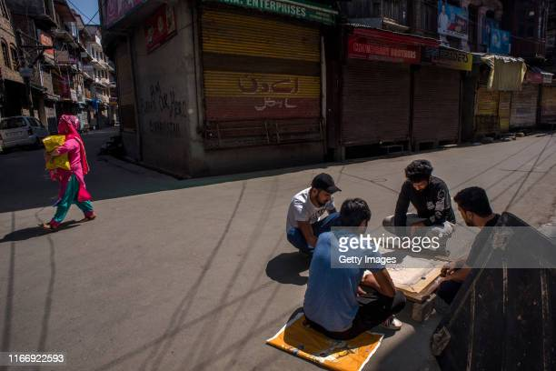 Kashmiri boys play a carom board game in middle of the road in the closed commercial hub of the city center during curfew like restrictions on...