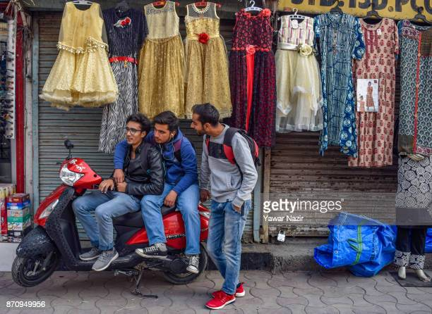 Kashmiri boys rest on a scooter next to a shuttered shop in a market on November 06 2017 in Srinagar the summer capital of Indian administered...