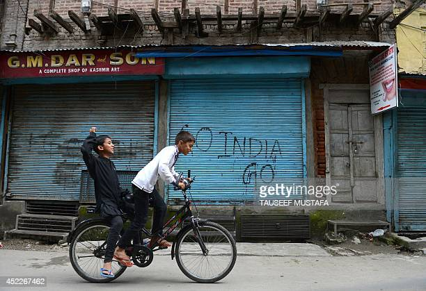 Kashmiri boys ride a bicycle during a oneday strike against Israeli military operations in Gaza in Srinagar on July 17 2014 A oneday strike was...