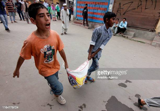 Kashmiri boys shout profreedom as they carry stones for protesters during a protest against India's revoking of Article 370 of its constitution in...
