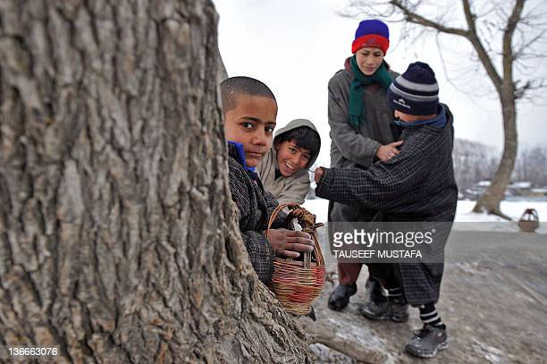 Kashmiri boys sit on a tree trunk holding traditional heating pots called Kangir to warm themselves in Srinagar on January 10,2012. A cold wave...