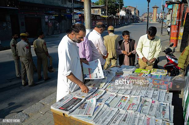 Kashmiri buy newspaper from a hawker after Indian authorities lifted a threeday ban on the publication of local newspapers during a curfew following...
