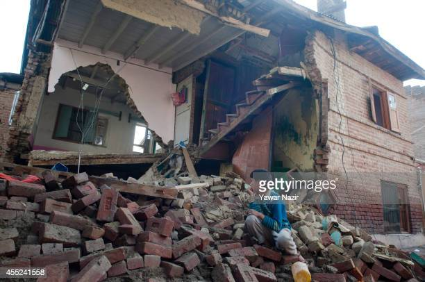 Kashmiri child looks at a residential house collapsed in a flooded area on September 11 2014 in Srinagar the summer capital of Indian administered...