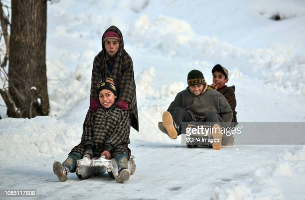 Kashmiri children seen sliding down a hill on sledges during a sunny winter day in Ganderbal about 50kms from Srinagar Indian administered Kashmir...