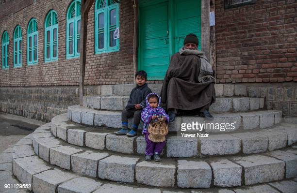 Kashmiri children sit with a man on the porch of a mosque in a remote village during a cold day on January 04 2018 in Kulhom north of Srinagar the...