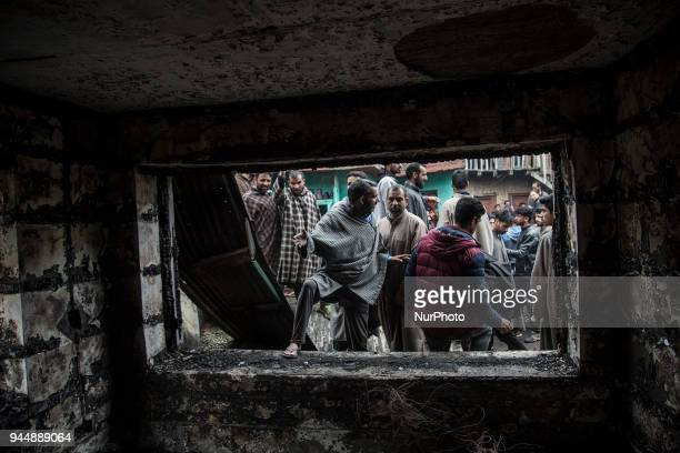 Kashmiri civilians check the burnt house where rebels took the shelter while fighting with the government forces Wednesday April 11 in Khudwani...