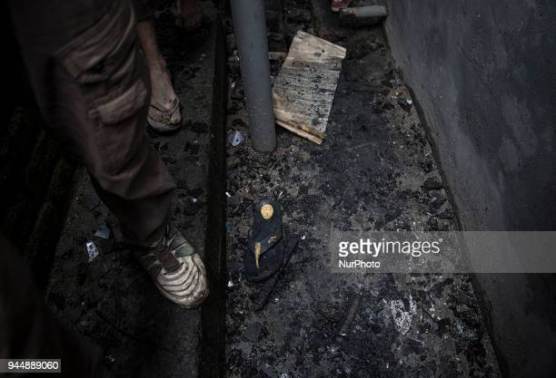 Kashmiri civilians check the burnt houses where rebels took the shelter while fighting with the government forces Wednesday April 11 in Khudwani...