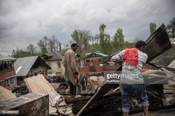 Kashmiri civilians search the debris of a house after a gunfight between rebels and government forces Wednesday April 11 in Khudwani village about 60...