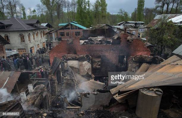 Kashmiri civilians search the debris of three house after a gunfight between rebels and government forces Wednesday April 11 in Khudwani village...