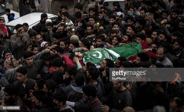Kashmiri civilians touch the body of Sharjeel Sheikh a civilian who was shot dead by Indian government forces during clashes near the gunfight site...