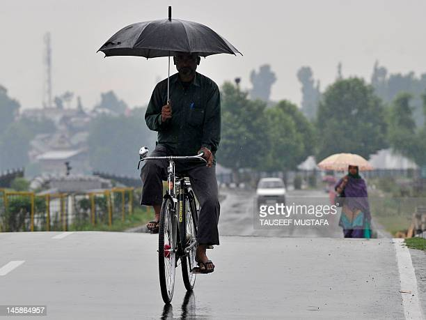 Kashmiri commuter rides his bicycle while holding an umbrella as it rains on the outskirts of Srinagar on June 7, 2012. Thousands of holiday goers...