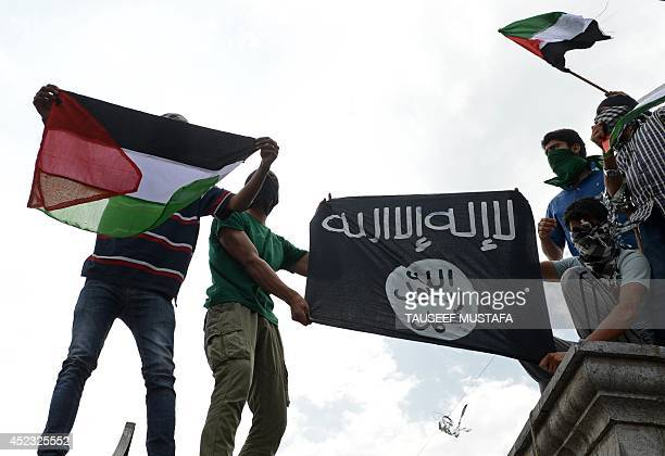 Kashmiri demonstrators hold up Palestinian flags and a flag of the Islamic State of Iraq and the Levant during a demonstration against Israeli...