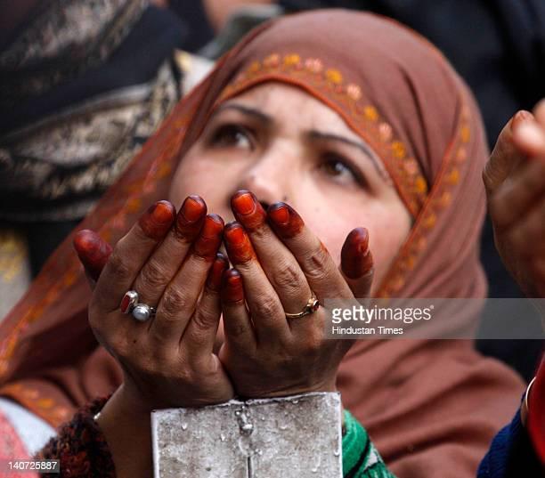Kashmiri devotee praying as their head priest displays a relic of Sufi Saint Syed Abdul Qadir Jilani during the anniversary of the saint's birth on...