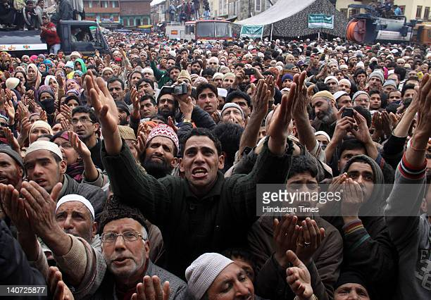 Kashmiri devotees pray as their head priest displays a relic of Sufi Saint Syed Abdul Qadir Jilani during the anniversary of the saint's birth on...