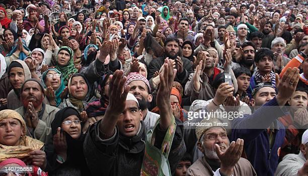 Kashmiri devotees pray as their head priest displays a relic of Sufi Saint Syed Abdul Qadir Jilani during the saint's birth anniversary on March 5...