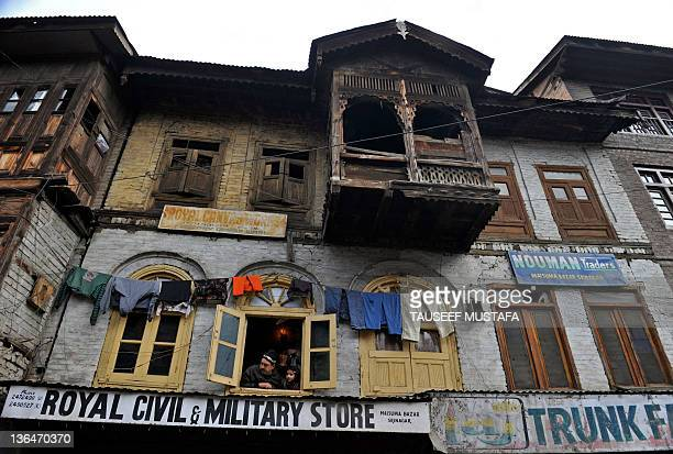 Kashmiri family watch from their window as Jammu and Kashmir Liberation Front supporters rally during a protest against the killing of an 18 year old...
