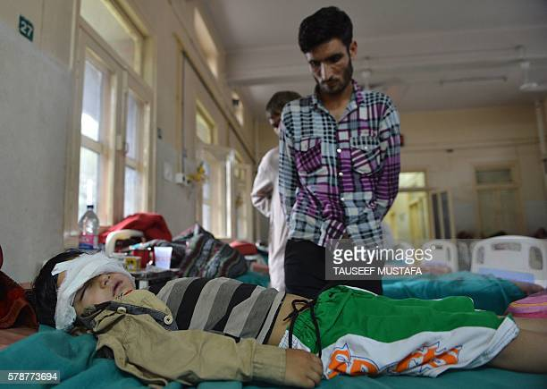 Kashmiri father of fiveyear old Nasir Ahmed Khan keeps watch at his bedside in a hospital in Srinagar on July 22 after the boy was allegedly beaten...
