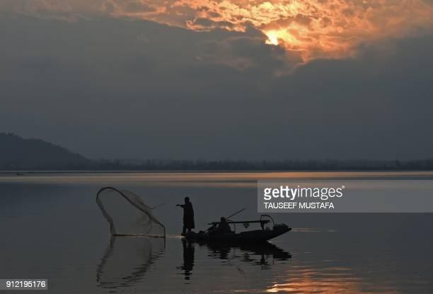 Kashmiri fisherman casts his net from his boat during sunset in Dal lake in Srinagar on January 30 2018 / AFP PHOTO / TAUSEEF MUSTAFA