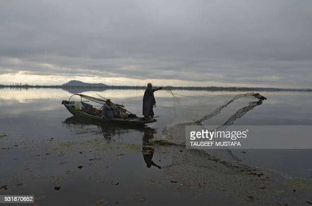 Kashmiri fisherman casts his net from his boat in Dal lake during cold and rainy day in Srinagar on March 14 2018 / AFP PHOTO / Tauseef MUSTAFA