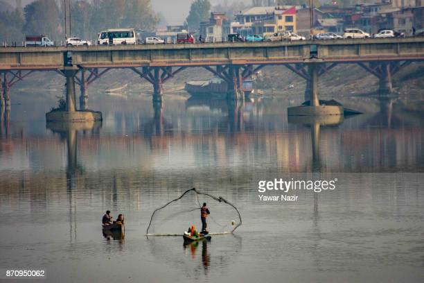 Kashmiri fisherman casts his net on the waters of river Jehlum on November 06 2017 in Srinagar the summer capital of Indian administered Kashmir...
