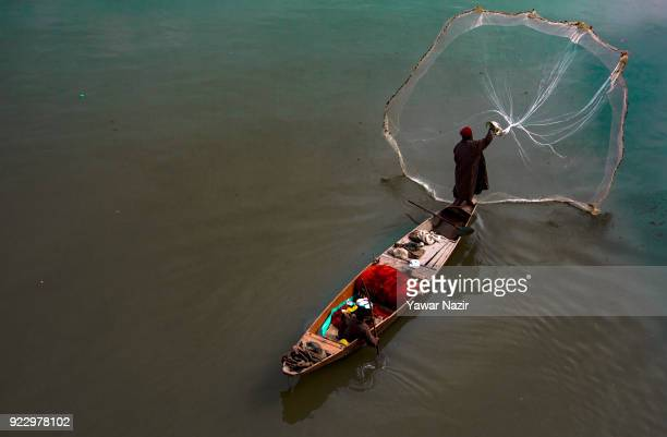 Kashmiri fisherman casts his net on the waters of river Jehlum on February 22 2018 in Srinagar the summer capital of Indian administered Kashmir...