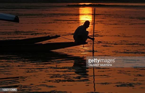 Kashmiri fisherman paddles his boat during sunset on Dal lake in Srinagar on September 12 2018