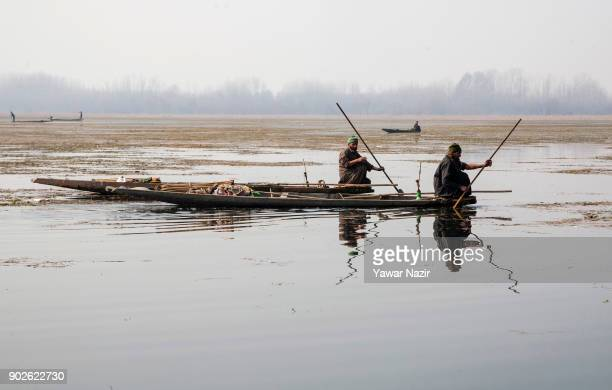 Kashmiri fishermen holding harpoons covered under blankets wait in their boats to catch fish by a unique technique called Tchaye gard shikar in the...