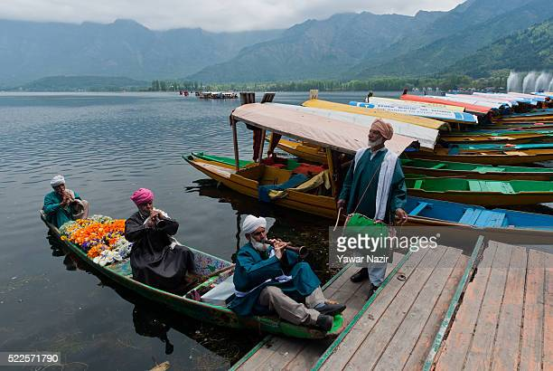Kashmiri folk dancers in traditional attire perform in a Shikara boat on the Dal lake during the Shikara boats festival on April 20 2016 in Srinagar...