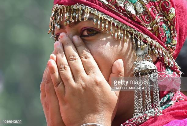 A Kashmiri girl dressed in traditional attire gestures during celebrations marking India's 72nd Independence Day at cricket Stadium in Srinagar on...