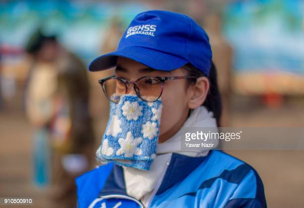 Kashmiri girl hides her face with handkerchief at the Sher i Kashmir stadium as she participates in the parade where the authorities held the main...