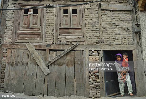 Kashmiri girl holds her brother in the doorway of their home while watching protesters shout profreedom and antiIndian slogans during mourning and...