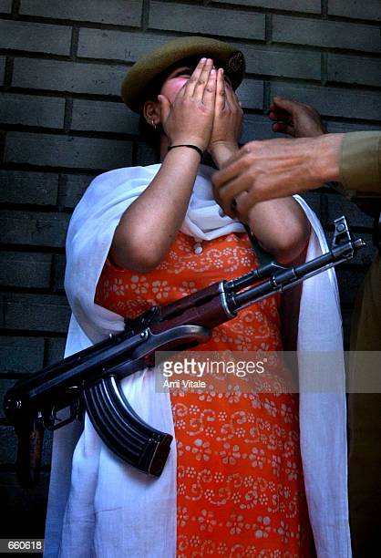 Kashmiri girl mourns the death of her uncle as she tries on his hat and gun on June 7 2002 in Srinagar the summer capital of the Indian held state of...