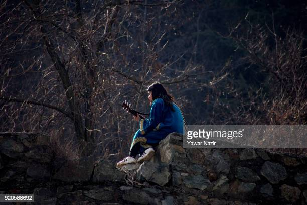 Kashmiri girl plays a guitar on a hillock during a warm winter day on February 19 2018 in Srinagar the summer capital of Indian administered Kashmir...