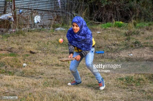 Kashmiri girl plays cricket during a cold day in Srinagar, the summer capital of Jammu and Kashmir.