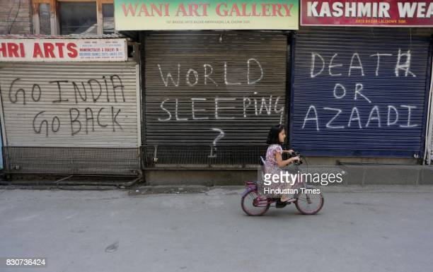 Kashmiri girl rides bicycle in front of closed shops during restrictions in a downtown area on August 11 2017 in Srinagar India Authorities imposed...
