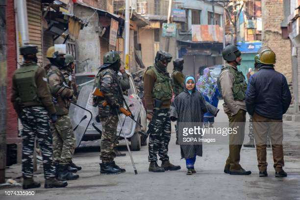 Kashmiri girl seen walking past the Indian army men standing on guard during the restrictions in Srinagar. Authorities imposed restrictions to...